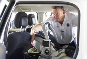 capt-bob-smallacombe-demostrates-the-space-needed-between-a-car-seat-and-the-drivers-seat-in-a-car