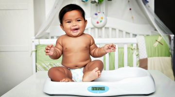 Feature | Cute baby boy on scale | Baby Weight Chart | How Much Should My Baby Weigh? [INFOGRAPHIC]