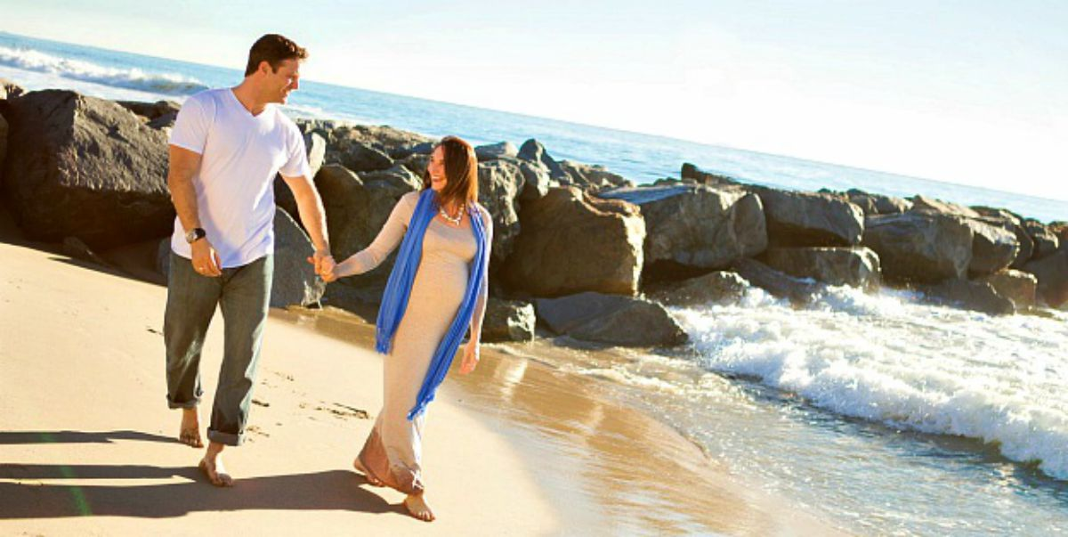 Happy couple walking in the beach while holding hands | Stunning Maternity Pictures, Ideas, And Photo Shoot Themes