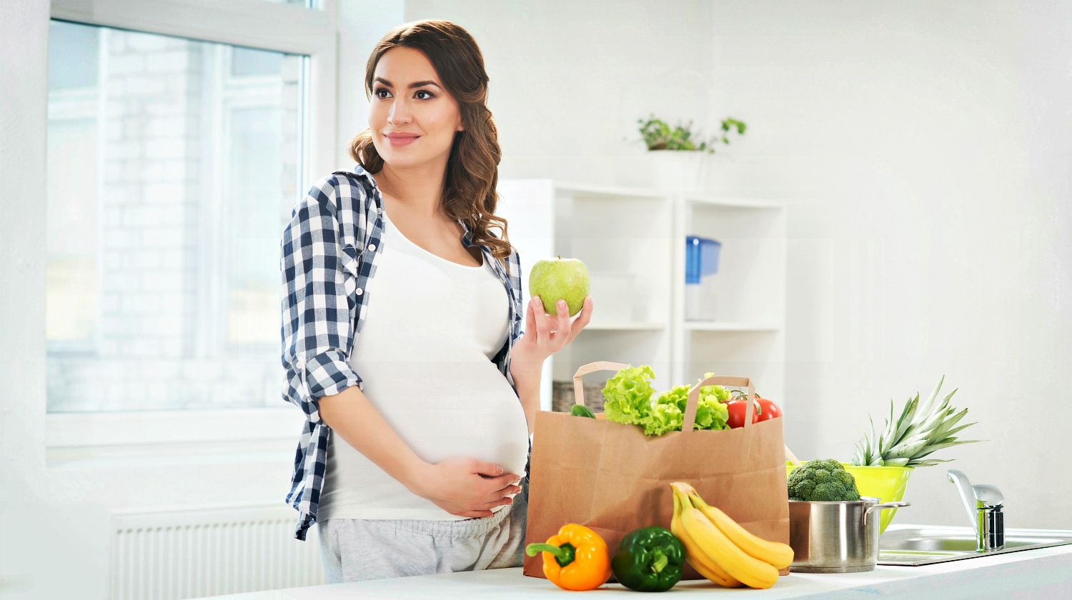 Feature | Pregnant woman in kitchen holding green apple and smiling | Pregnancy Diet and Nutrition FAQs
