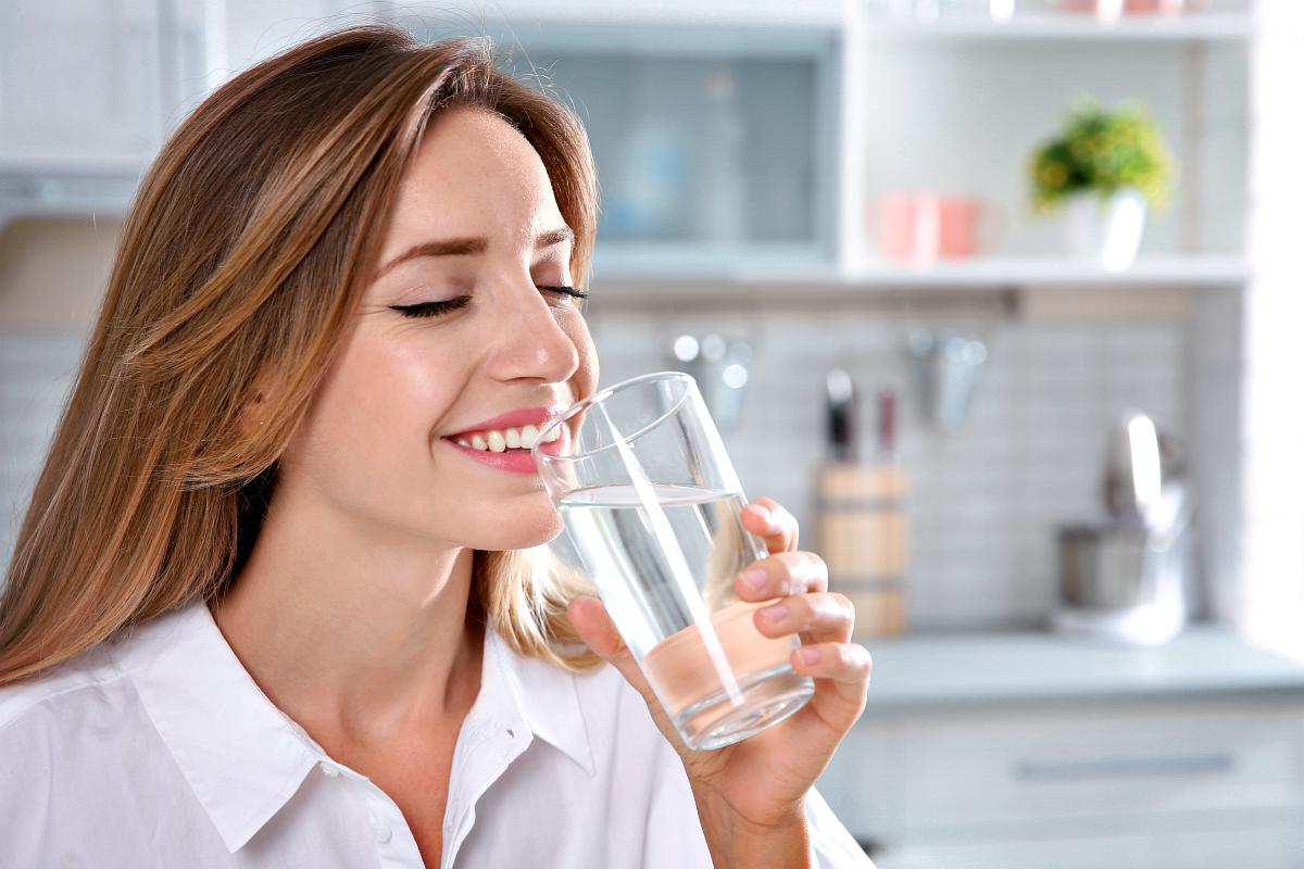 Woman drinking water from glass | Alkaline Water Benefits During Pregnancy